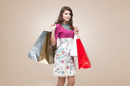 studio portrait of a beautiful young woman, in a colourful outfit, holding in her hands a few shopping bags. she is laughing and looking very happy. photo