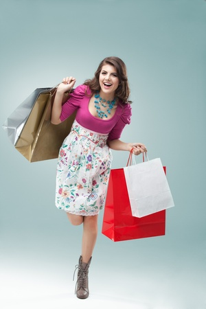 shopping bags: studio portrait of a beautiful young woman, in a colourful outfit, holding in her hands a few shopping bags. she is hopping on one foot, laughing and looking very happy.