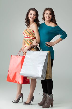 a studio image of two beautiful young women in high heels, holding a few shopping bags, smiling and looking happy.