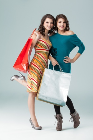 2 1 2: a studio image of two beautiful young women in high heels, holding a few shopping bags, smiling and looking happy.