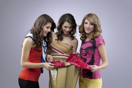women at shopping looking at a dress photo