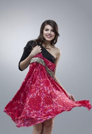 hair dress: chica intentando fower Roja vestido posando feliz Foto de archivo
