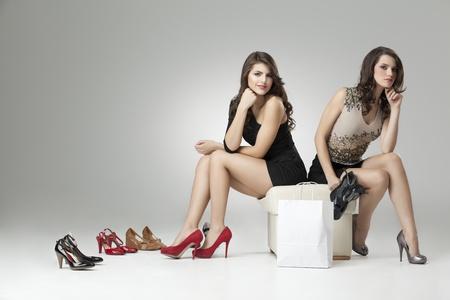 tacones rojos: dos mujeres glamorosas rojo gris tacones altos Foto de archivo