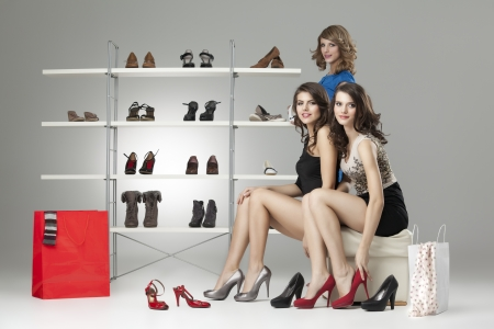 three young women sitting trying shoes looking happy Stock Photo