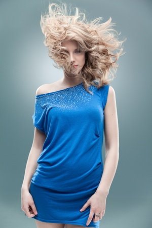 blonde curly hair: curly blonde woman blue dress Stock Photo