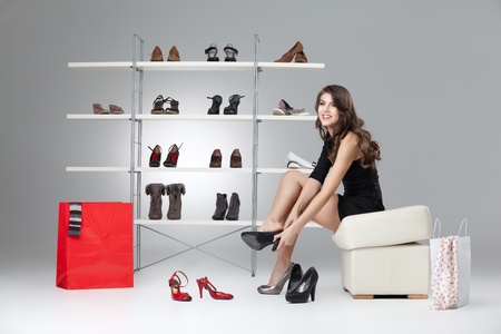 young woman trying on black high heels photo