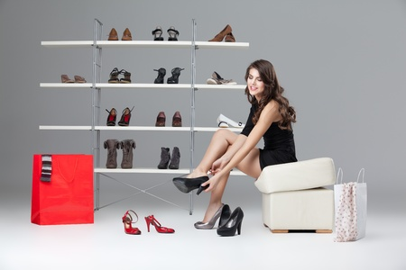 high heel shoe: young woman trying on black high heels
