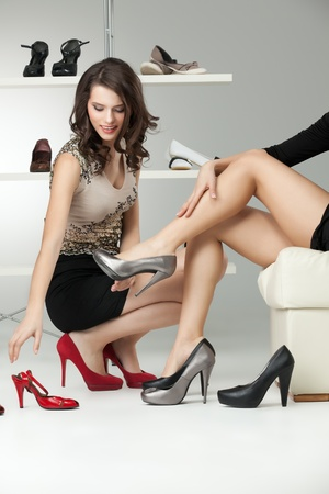 high fashion model: two young women trying on high heels