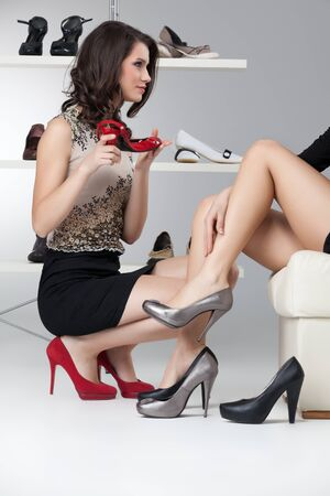 high heel shoes: two young women trying on high heels