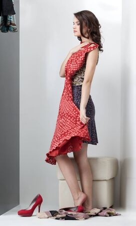 view an elegant wardrobe: brunette woman looking red dress in the mirror