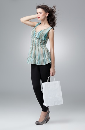 tall brunette woman shopping white bag wind