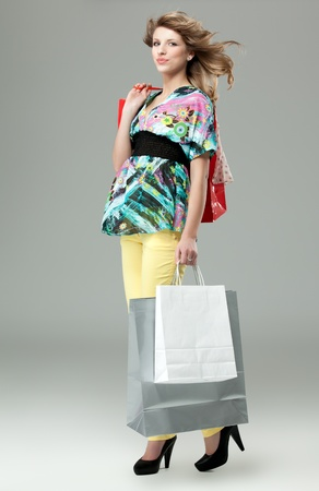blonde woman carrying shopping bags high heels photo