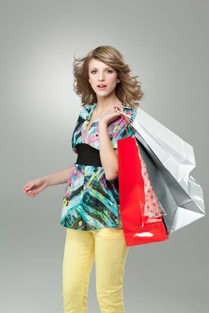 blonde woman carrying shopping bags wind hair photo