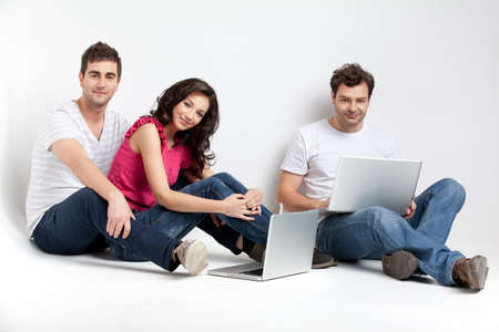 friends sitting down smiling at camera with laptops Stock Photo - 9887597