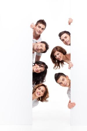 vertical: Grupo de j�venes de gente sonriendo detr�s de banner de publicidad Foto de archivo