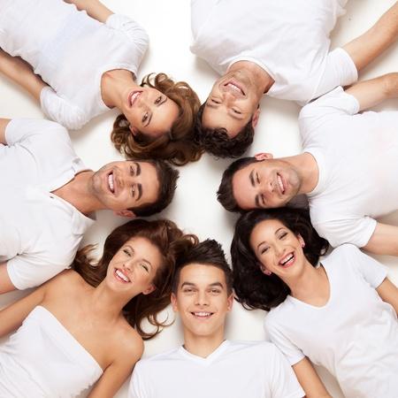 amistad: Grupo de gente joven sonriendo en c�rculo  Foto de archivo
