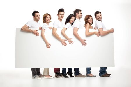 billboard advertising: group of smiling friends holding white banner  Stock Photo