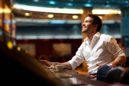 slots: sonriendo el hombre guapo, con la esperanza de ganar en tragaperras