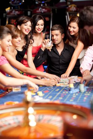 roulette player:  glamourous laughing friends plying betting at roulette table