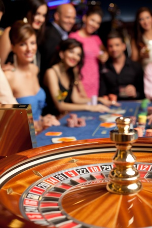 roulette wheels: group of young smiling people looking excited at spinning roulette Stock Photo