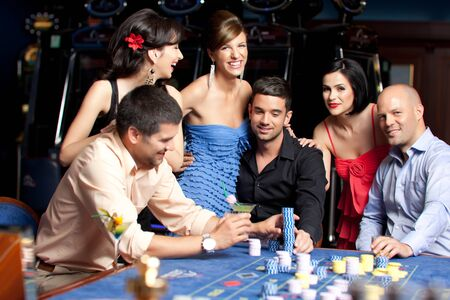 roulette player: young people sitting at the roulette casino table talking Stock Photo