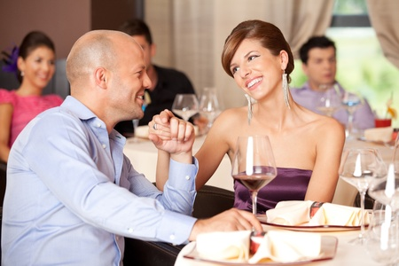 young smiling couple romancing at a restaurant table  photo