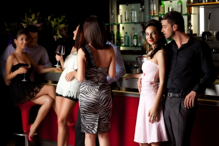 young man and woman flirting beside bar in a club