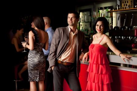 coquetear: hombre y mujer sentada feliz junto a la barra de la discoteca