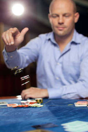 handsome confident man playing poker throwing chips  photo