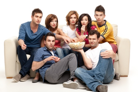 horror movies: friends sitting on couch watching tv eating popcorn expressions  Stock Photo