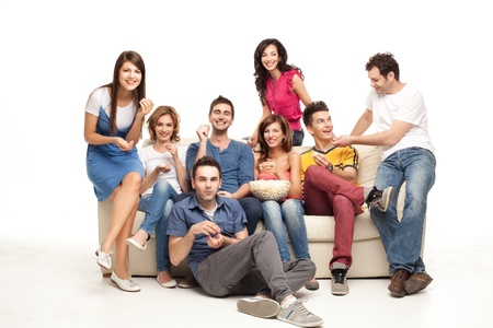 friends laughing: friends sitting on couch laughing at comedy movie Stock Photo
