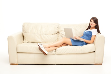 young brunette woman laying comfortable with laptop on couch photo
