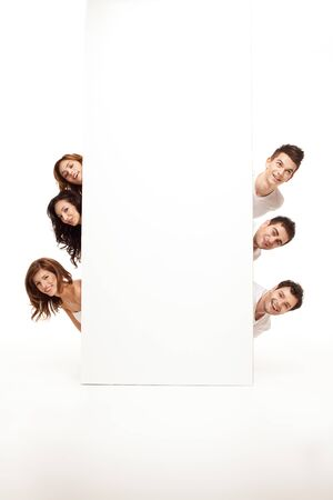 personas de pie: equipo de sonriente amigos ocultar sobre un banner ad en blanco Foto de archivo