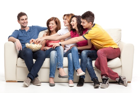 bowls of popcorn: friends sitting on couch reaching for the popcorn bowl