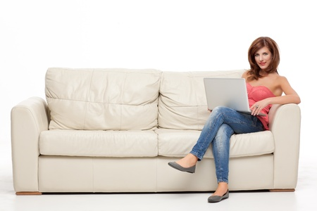 red sofa: young brunette woman sitting comfortable with laptop on couch Stock Photo