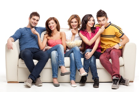 friends feeding popcorn to each other while sitting couch photo
