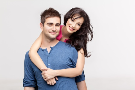 lovers embracing: woman holding with love her boyfriend from behind, posing at camera Stock Photo
