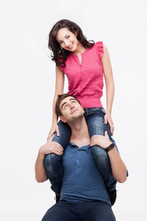 Portrait of young man holding his happy girlfriend on shoulders Stock Photo - 9937459