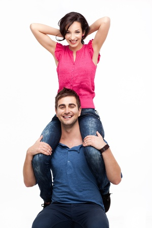 Portrait of young man holding his happy girlfriend on shoulders photo
