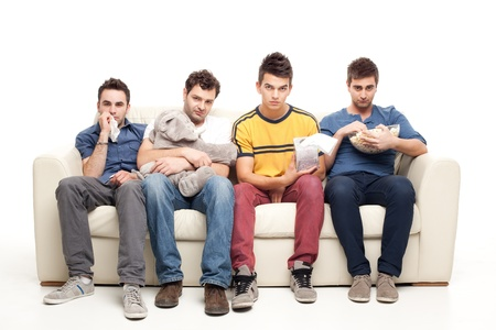 seeing: sad  group of young men looking at television sitting on a couch