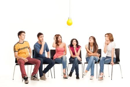 Grupo de amigos reflexionando sobre una bombilla Foto de archivo