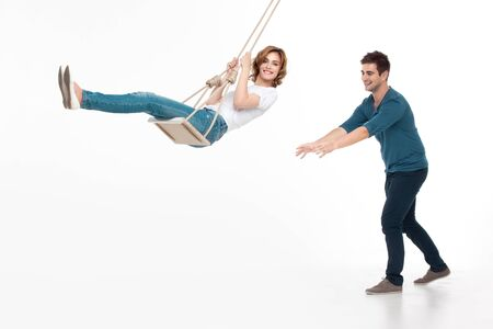 griping: young handsome man pushing his girlfriend on a swing