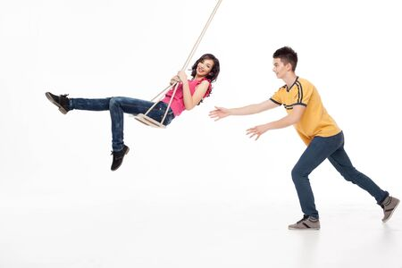 young handsome man pushing his girlfriend on a swing photo