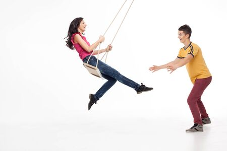 griping: young handsome man catching his swinging girlfriend