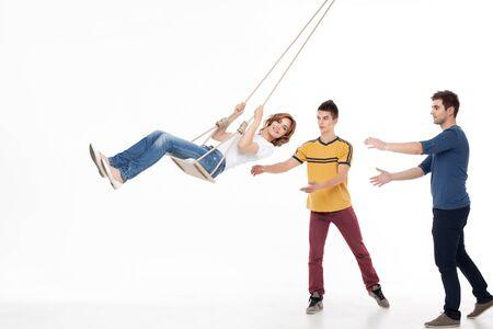 handsom: dos hombres handsom empujando hacia la mujer sonriente un swing