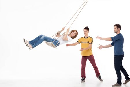 rocked: two handsom men pushing on the swing one smiling woman  Stock Photo