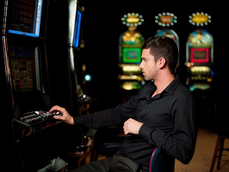 lucky man: man playing the slot machin, watching carefuly
