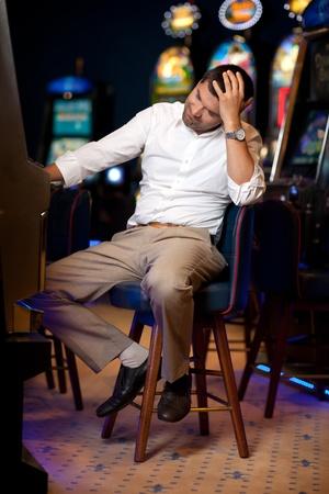 tragamonedas: hombre tocando tragaperras en un casino de noche, aburrido
