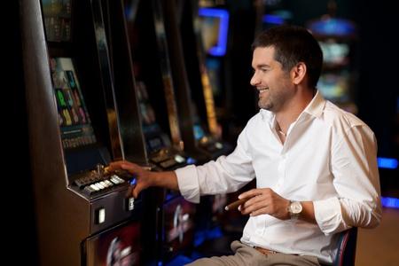 tabaco: apuesto hombre sonriente con la esperanza de ganar en tragaperras