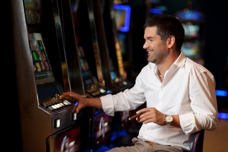 slot: smiling handsome man hoping to win at slot machine